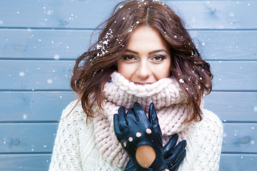 48119316 - winter portrait of young beautiful brunette woman wearing knitted snood covered in snow. snowing winter beauty fashion concept.
